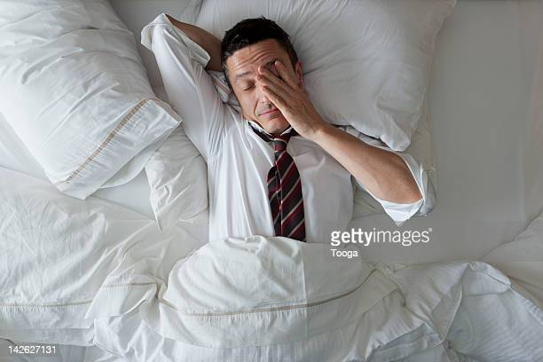 Businessman in bed with clothes on