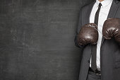 Businessman in boxing gloves and suit on blackboard background