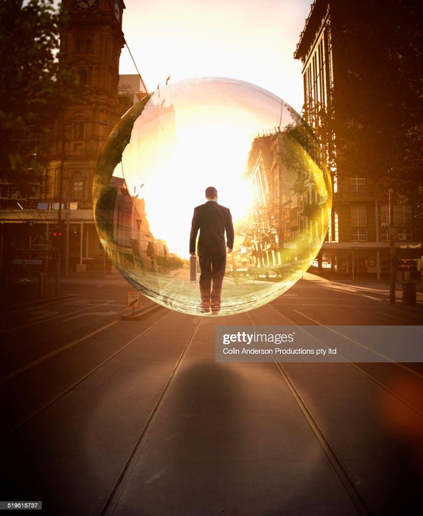 Businessman in bubble walking on city street : Stock Photo