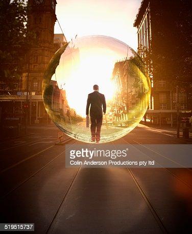 Businessman in bubble walking on city street