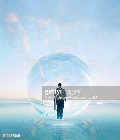 Businessman in bubble walking on water