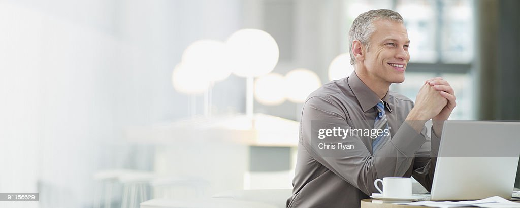 Businessman in cafeteria with laptop : Stock Photo