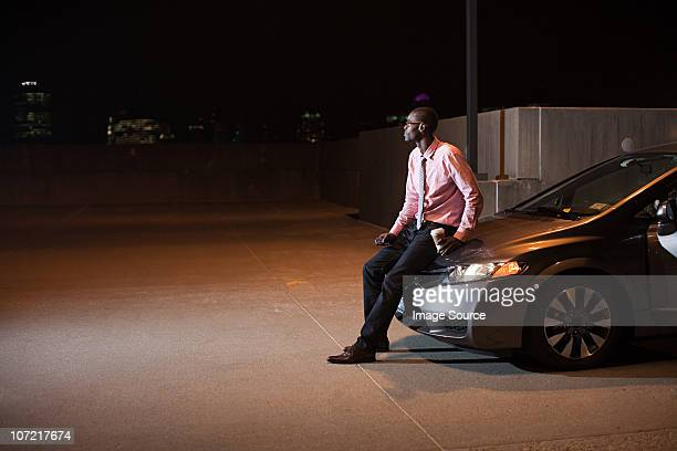 Businessman in car park at night