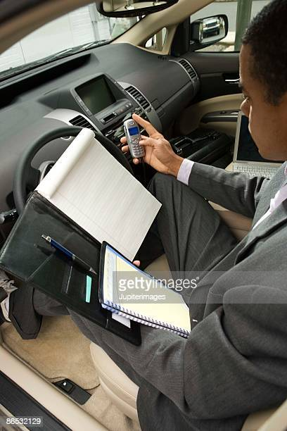 Businessman in car with cell phone and appointment book