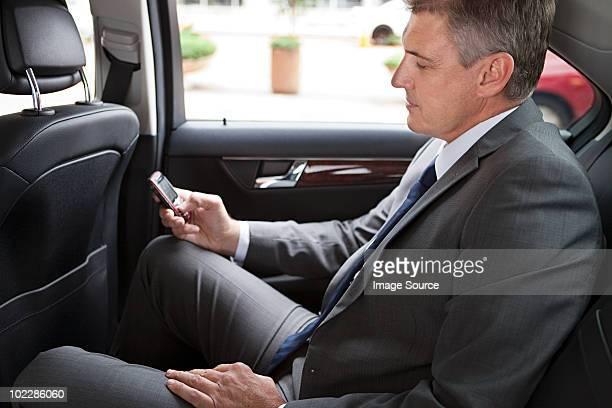 Geschäftsmann in Auto mit cellphone