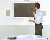 Businessman in conference room, gesturing towards screen on wall