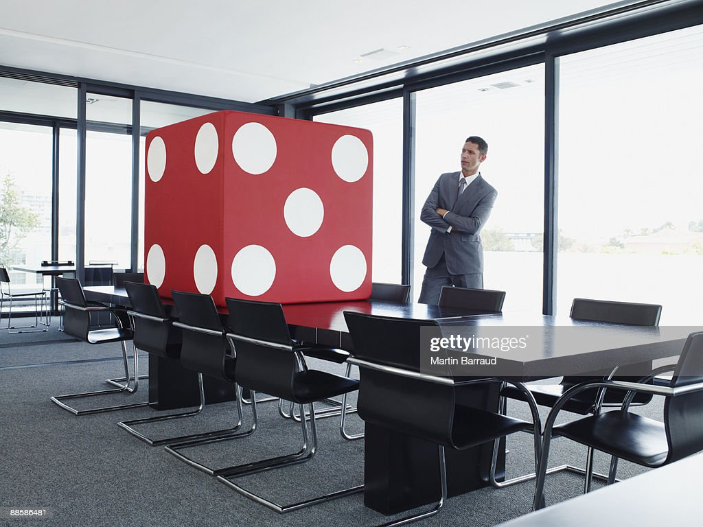 Businessman in conference room looking at giant dice : Stock Photo