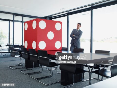 Businessman in conference room looking at giant dice : Foto stock