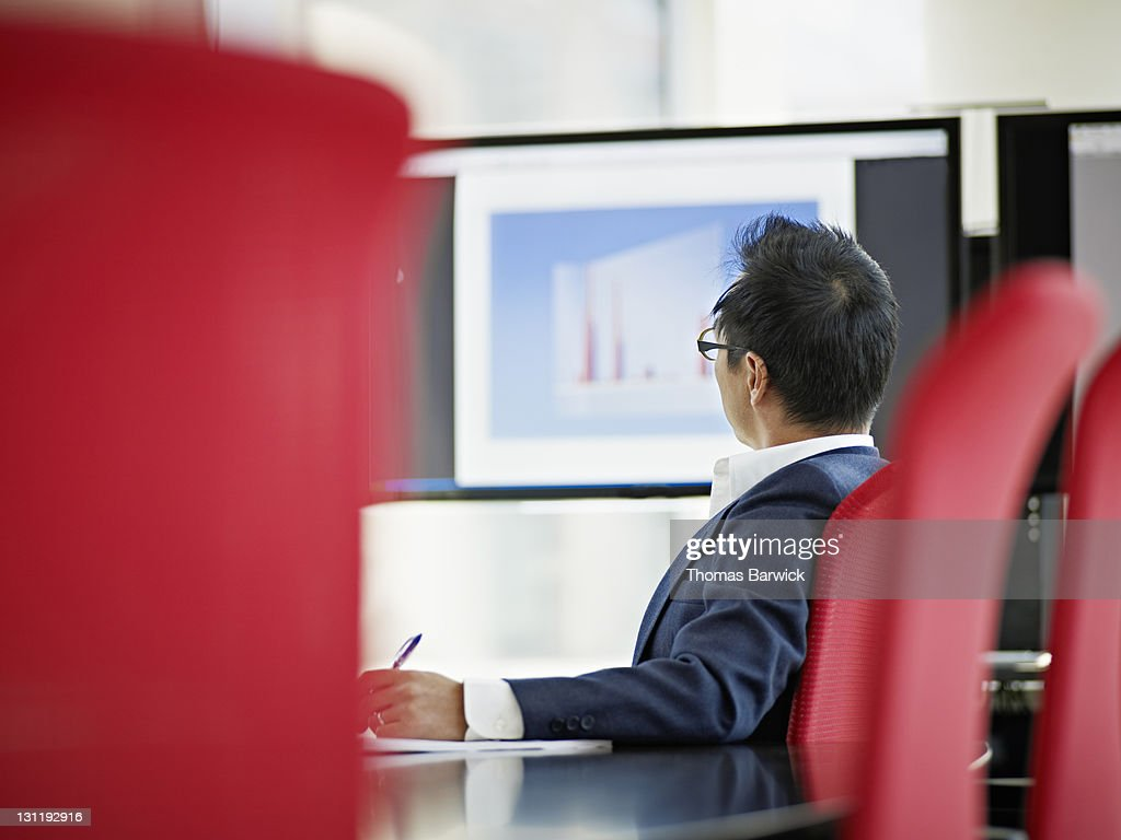 Businessman in conference room looking at graphs : Stock Photo