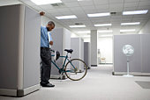 Businessman in cubicle with bicycle