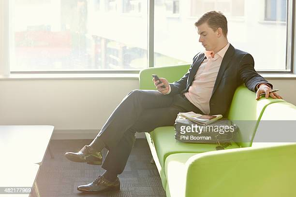 Businessman in departure lounge using cell phone