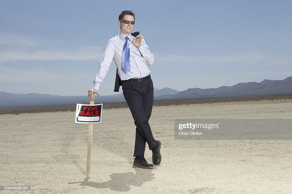 Businessman in dry lake bed leaning on 'for sale' sign : Stock Photo