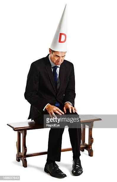 Businessman in dunce cap being punished sitting on naughty chair