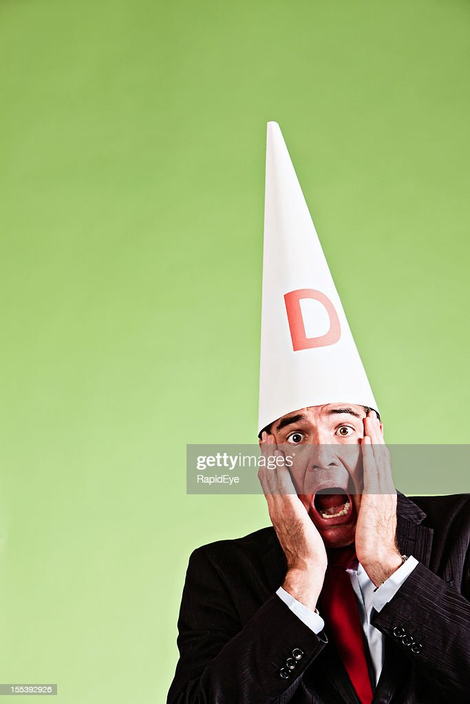 Businessman in dunce cap has done something stupid!