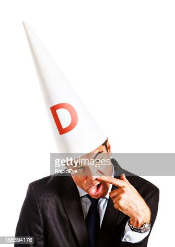 Businessman in dunce cap makes stupid face: work is insane!