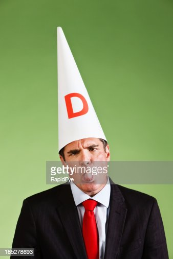 Businessman in Dunce cap sticks out his tongue