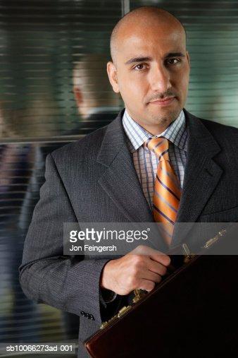 Businessman in elevator holding briefcase, smiling, portrait