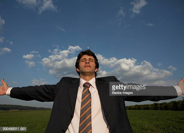 Businessman in field spreading arms wide