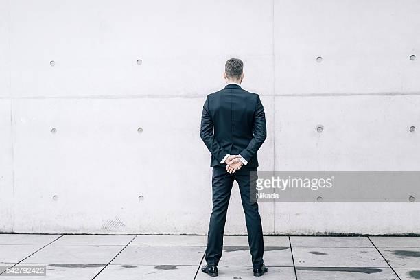 Geschäftsmann vor einem Betonwand