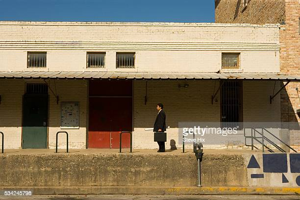 Businessman in Front of a Rundown Building