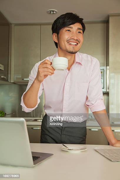 Businessman in front of his computer drinking coffee at home