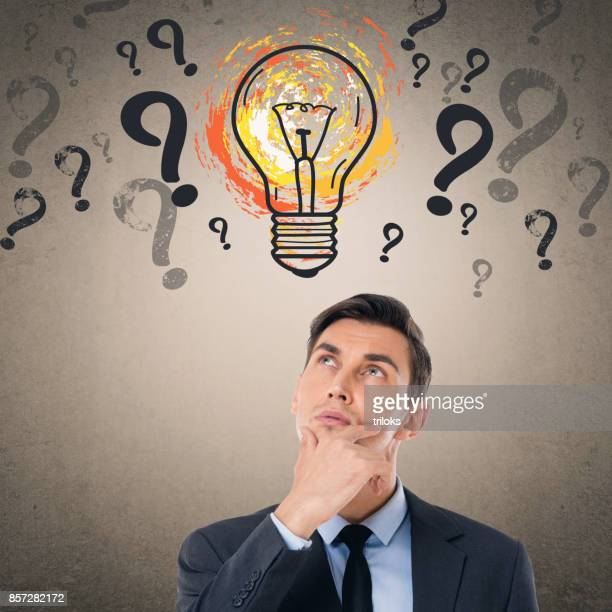 Businessman in front of light bulb icon on wall