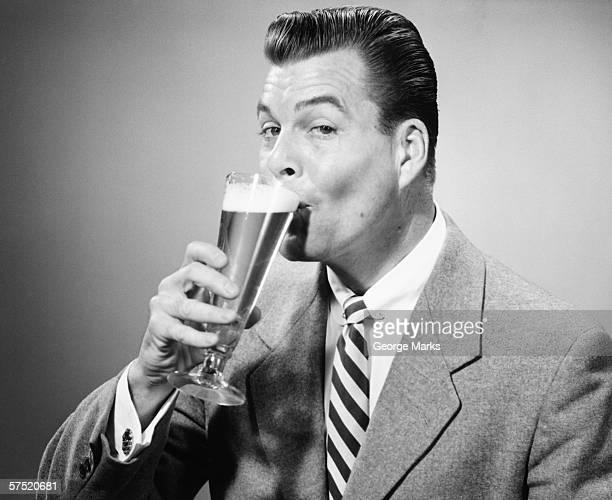 Businessman in full suit drinking beer in studio, (B&W), portrait