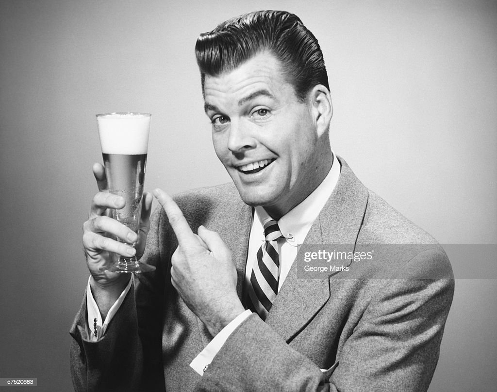 Businessman in full suit in studio pointing at glass of beer, (B&W), portrait : Stock Photo