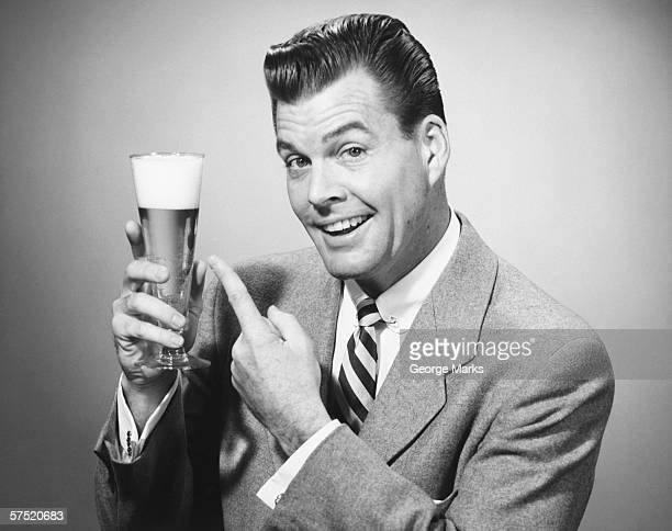 Businessman in full suit in studio pointing at glass of beer, (B&W), portrait