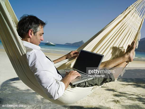 Businessman in hammock using laptop