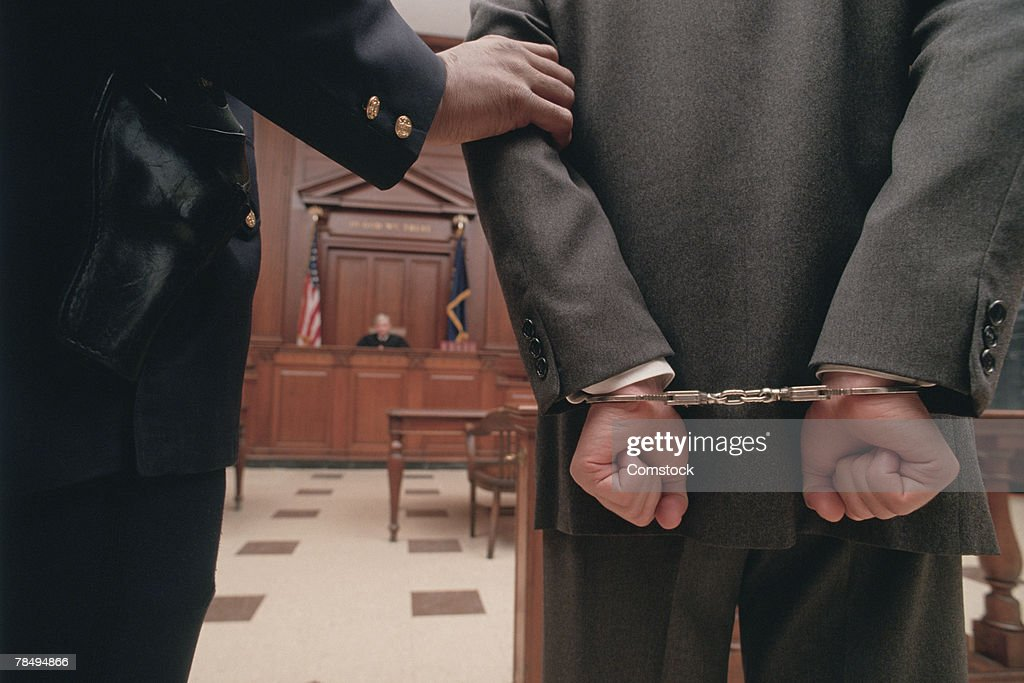 Businessman in handcuffs in courtroom