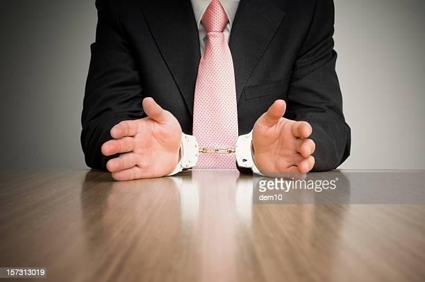 Geschäftsmann, sitzen am Tisch in Handschellen