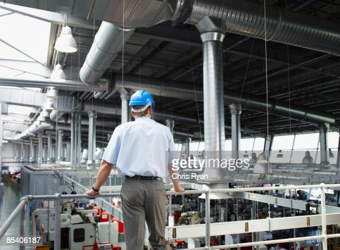 Businessman in hard-hat looking at factory floor : Stock Photo