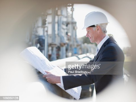 Businessman in hard-hat reviewing blueprints outdoors : Stock Photo