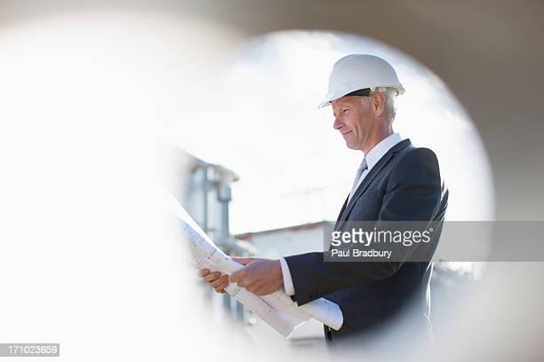 Hombre de negocios con duro sombrero revisar blueprints al aire libre