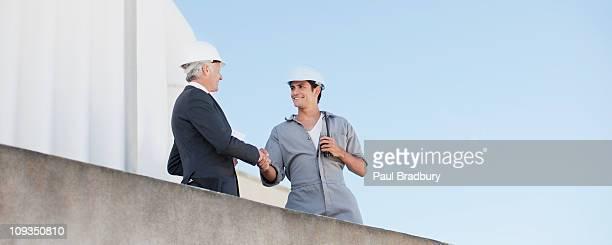 Geschäftsmann in harten-Hut Schütteln von hand mit Arbeiter im Freien