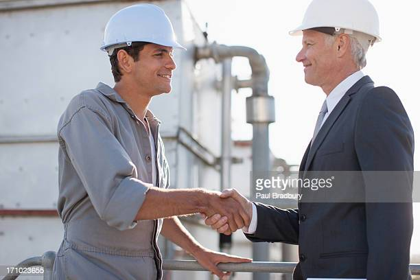 Geschäftsmann in schwer hat beim Händeschütteln mit Arbeiter im Freien
