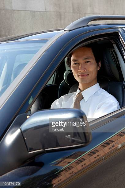 A businessman in his car, looking at camera
