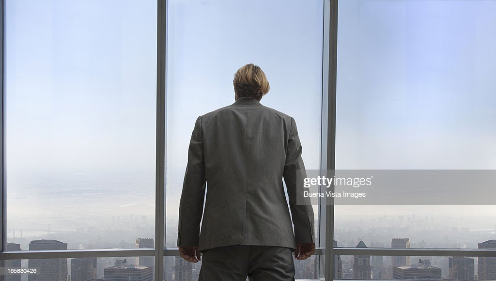 businessman in his office overlooking a city : Stock Photo
