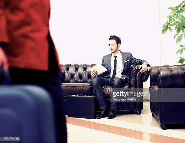 Businessman in hotel lobby with tablet