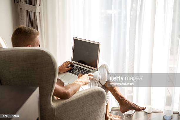 Businessman in hotel room working on laptop