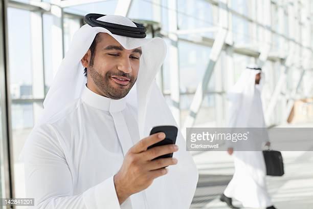 Businessman in kaffiyeh text messaging