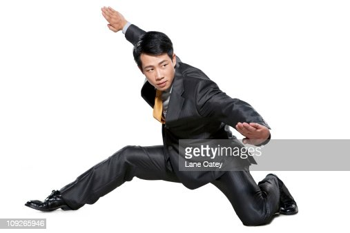 Businessman in martial arts crouching stance