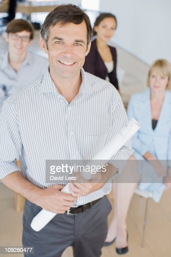 Businessman in meeting, coworkers in background : Stock Photo