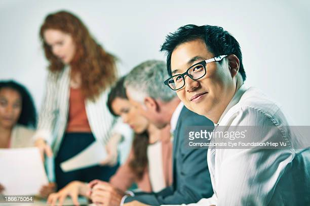Businessman in meeting, looking at camera