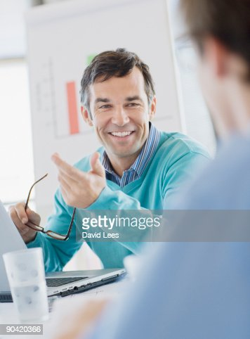 Businessman in meeting, smiling : Stock Photo
