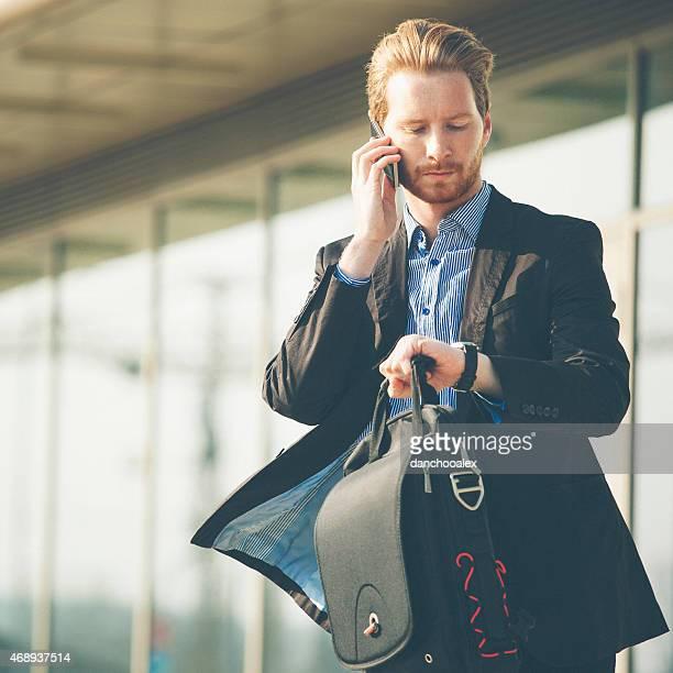 Giovane uomo d'affari Controlla tempo e parlare sul telefono cellulare