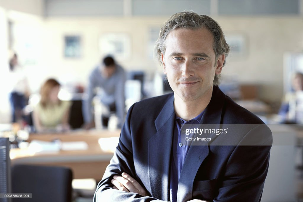 Businessman in office, arms crossed, smiling, portrait : Stock Photo