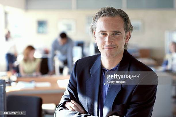 Businessman in office, arms crossed, smiling, portrait