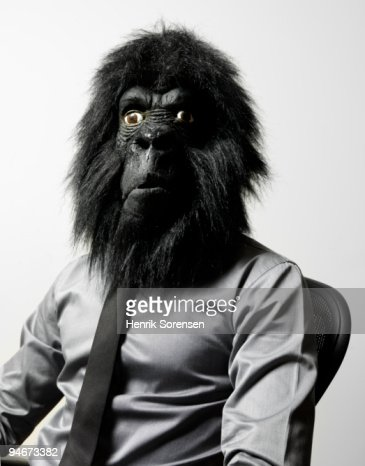 Businessman in office chair in gorilla mask